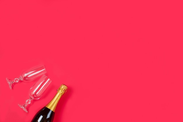 Bottle of a champagne and two champagne glasses on red background.