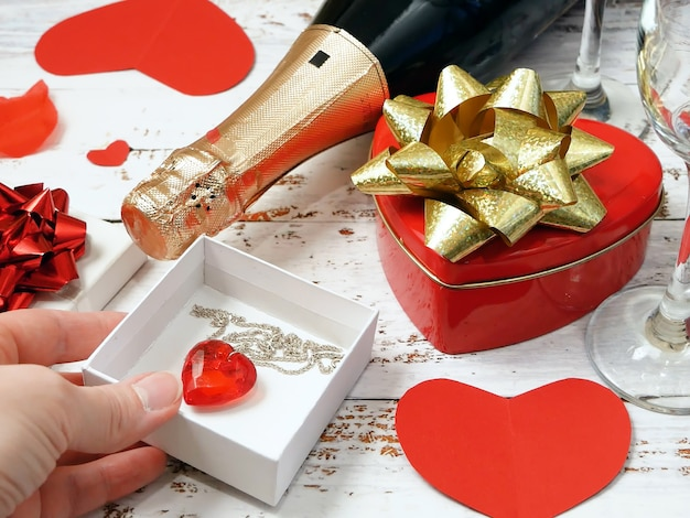Bottle of champagne, two glasse, and red pendant heart as gift