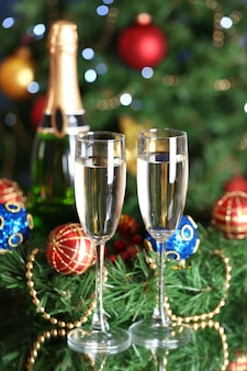 Bottle of champagne with glass and christmas balls on christmas tree background