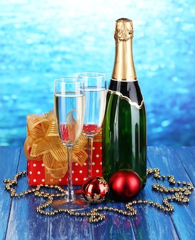 Bottle of champagne with glasses and christmas balls on wooden table on blue background