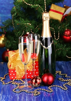Bottle of champagne with glasses and christmas balls on wooden table on christmas tree background