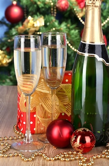 Bottle of champagne with glasses and christmas balls on wooden table on christmas tree