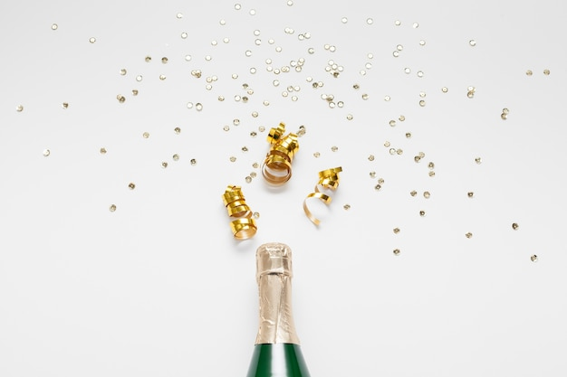 Bottle of champagne with glitter and confetti