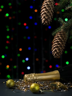 Bottle of champagne with yellow balloons under a christmas tree. happy new year