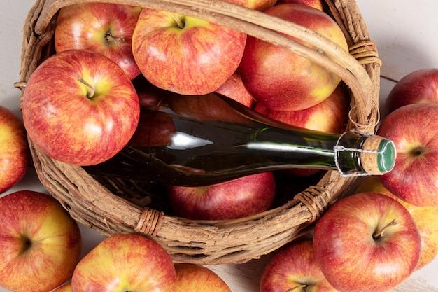 Bottle of cider and apples in basket