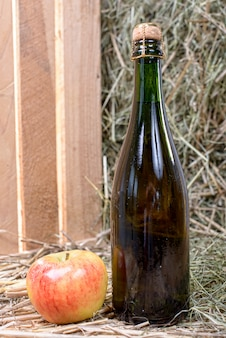 Bottle of cider with a apple and straw