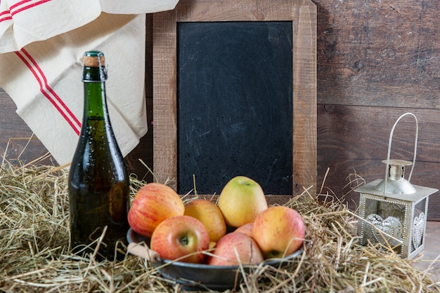 Bottle of cider with apples on the straw, and school chalkboard