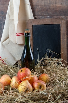 Bottle of cider with apples on the straw