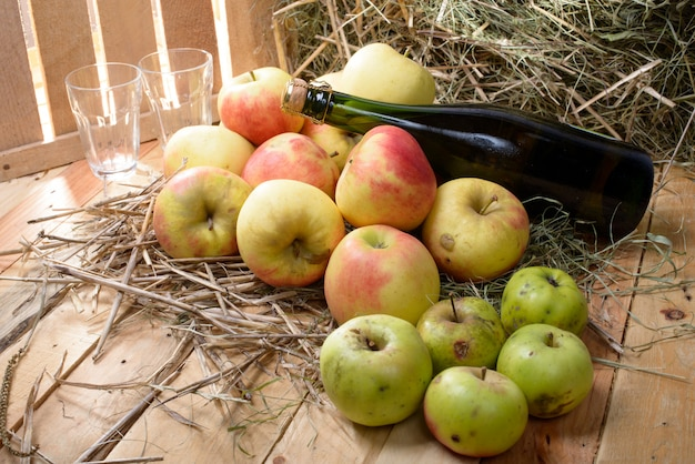 Bottle of cider with some apples and straw