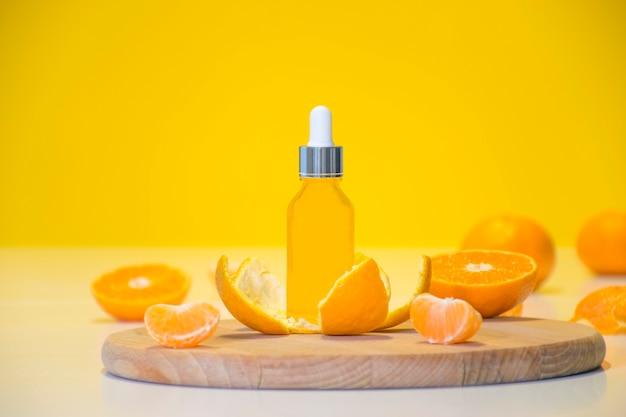 みかんの皮に柑橘系のエッセンシャルオイルをボトルに入れ、コピースペースのある黄色の背景にオレンジ色のピースを入れます。