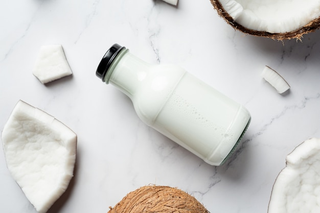 Bottle of coconut milk put on white marble background
