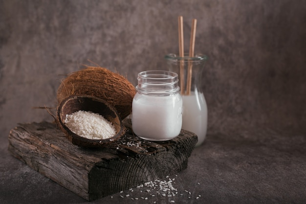 Bottle of coconut vegan milk, coco oil, whole coconut and flakes on dark background. clean eating and healthy food concept.