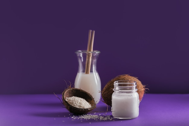 Bottle of coconut vegan milk, coco oil, whole coconut and flakes on violet