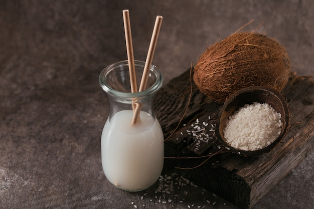 Bottle of coconut vegan milk with straws, whole coconut and flakes on a dark background. healthy lifestyle concept.