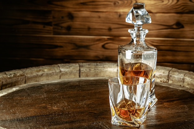 A bottle of cognac and glass on a brown wooden table. brandy