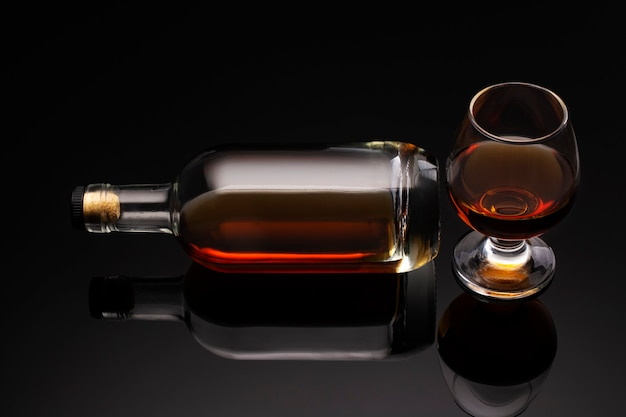 A bottle of cognac and a glass on a dark background