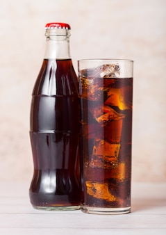 Bottle of cola soda drink with glass and ice cubes