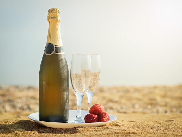 A bottle of cold champagne glasses and strawberries on a sandy beach.
