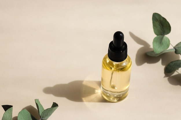 Bottle of cosmetic essential oil closeup with deep shadows hard light selective focus