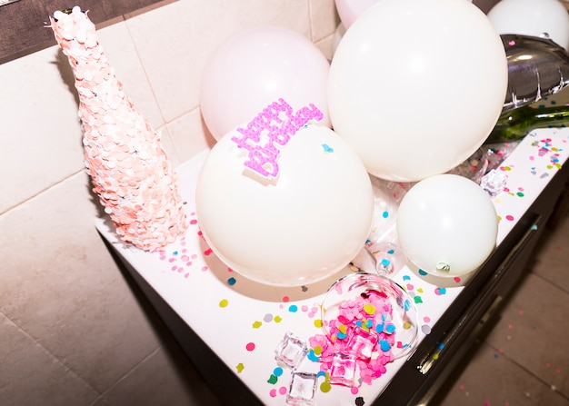 Bottle covered with pink confetti against white balloon