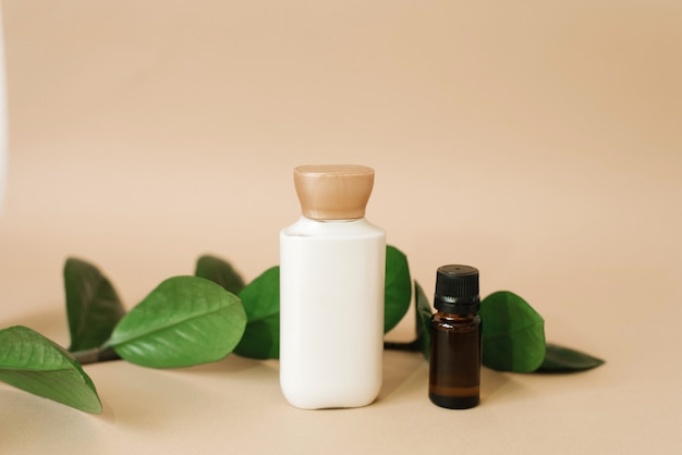 A bottle of cream for skin care for the face or body, a brown glass bottle with oil and leaves of zamiokulkas on a beige background. organic cosmetic products