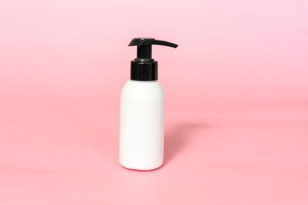 Bottle for cream with dispenser on pink background