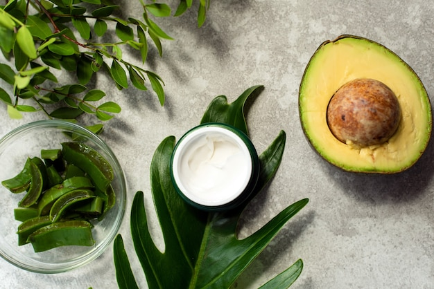 Bottle of cream with half an avocado and natural greens on marble background, top view