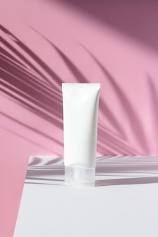 Bottle of cream with palm leaf shadow on pink surface