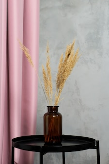 Bottle of dark brown glass and dry branches of pampas grass against background of pale pink curtains and dark concrete wall.