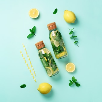 Bottle of detox water with mint, lemon on blue background.