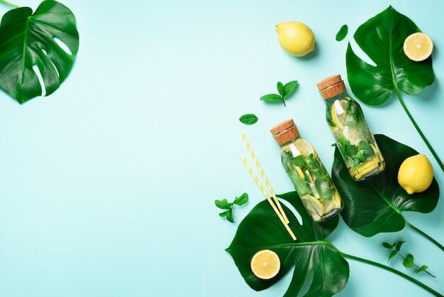 Bottle of detox water with mint, lemon and tropical monstera leaves on blue background.