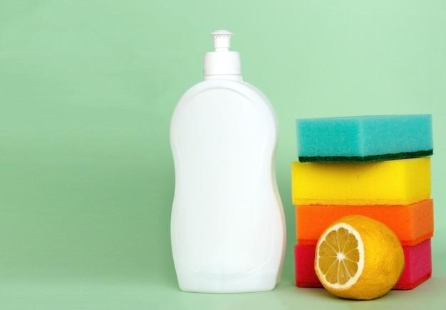 Bottle of dishwashing liquid sponges and lemon on color background