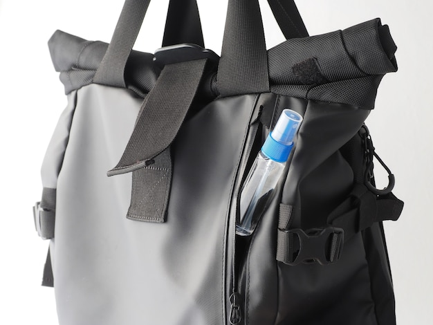 Bottle of disinfecting alcohol spray in modern black backpack.