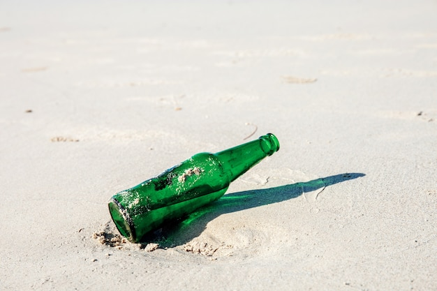 Bottle of drink on sand.