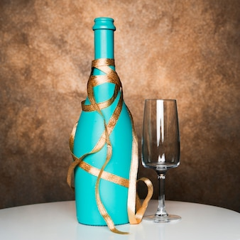 Bottle of drink with ribbon near glass on board