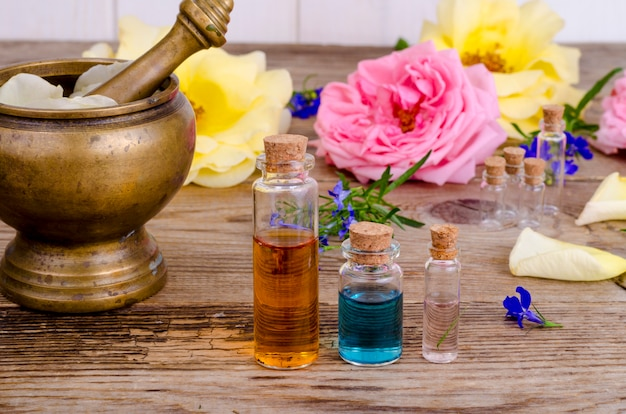 Bottle of essential oil for aromatherapy with fresh rose flowers.