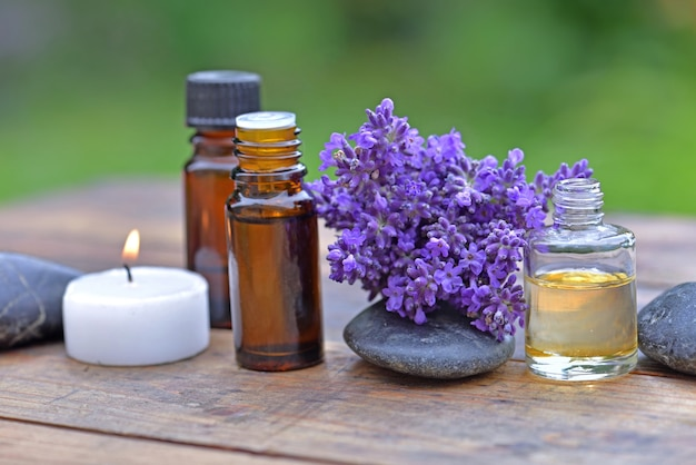 Bottle of essential oil and bouquet of lavender flower arranged on a wooden table with a candle