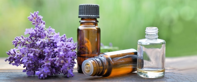 Bottle of essential oil and bouquet of  lavender flower arranged on a wooden table