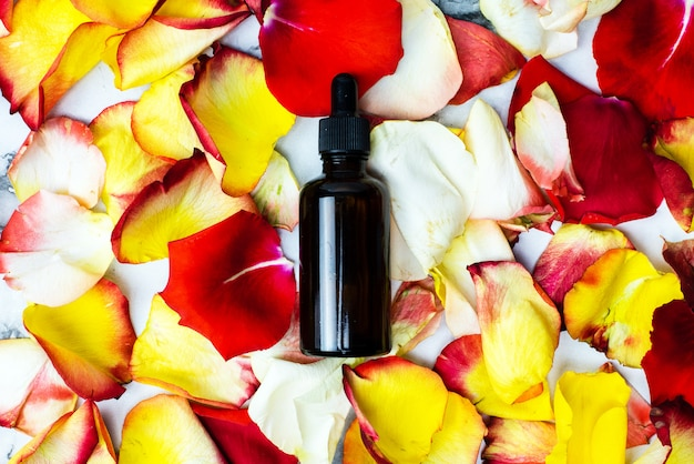 A bottle of essential oil on colorful petals