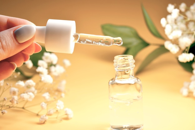 Bottle of essential oil and flowers