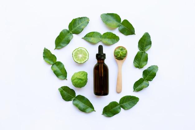 Bottle of essential oil and  fresh kaffir lime or bergamot fruit with leaves