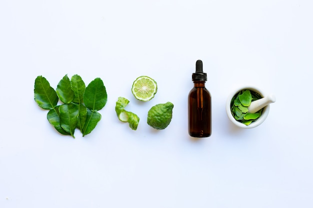 Bottle of essential oil and  fresh kaffir lime or bergamot fruit with leaves