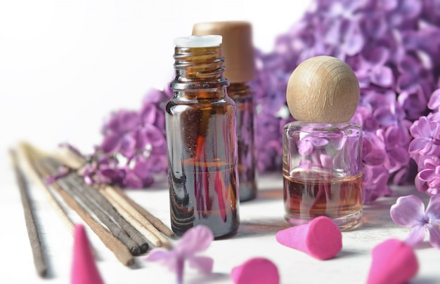 Bottle of essential oil and incense with purple lilac flower