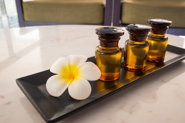 Bottle of essential oil and jasmin flower with plumeria flower setup on marble table.