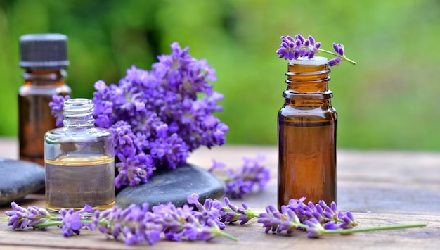 Bottle of essential oil and  lavender flowers arranged on a wooden table in garden