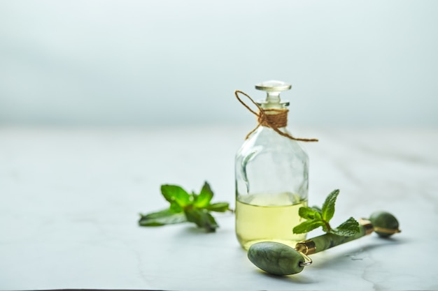 Bottle of essential oil of mint and green leaves and jade massage roller for the face natural organic ingredients for cosmetics skin care body care beauty care concept