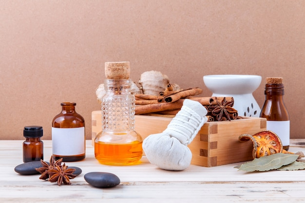 Bottle of essential oil with cinnamon stick on old wooden background .