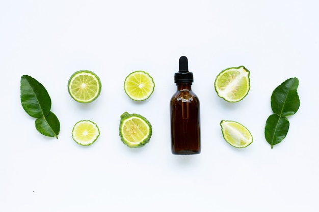 Bottle of essential oil with fresh kaffir lime or bergamot fruit