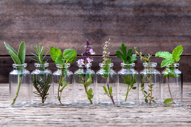 Bottle of essential oil with herbs set up on old wooden background .