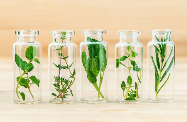 The bottle of essential oil with herbs on wooden background .
